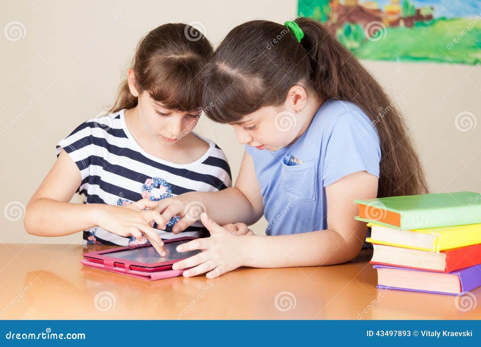 Deux petites filles mignonnes d école avec la Tablette