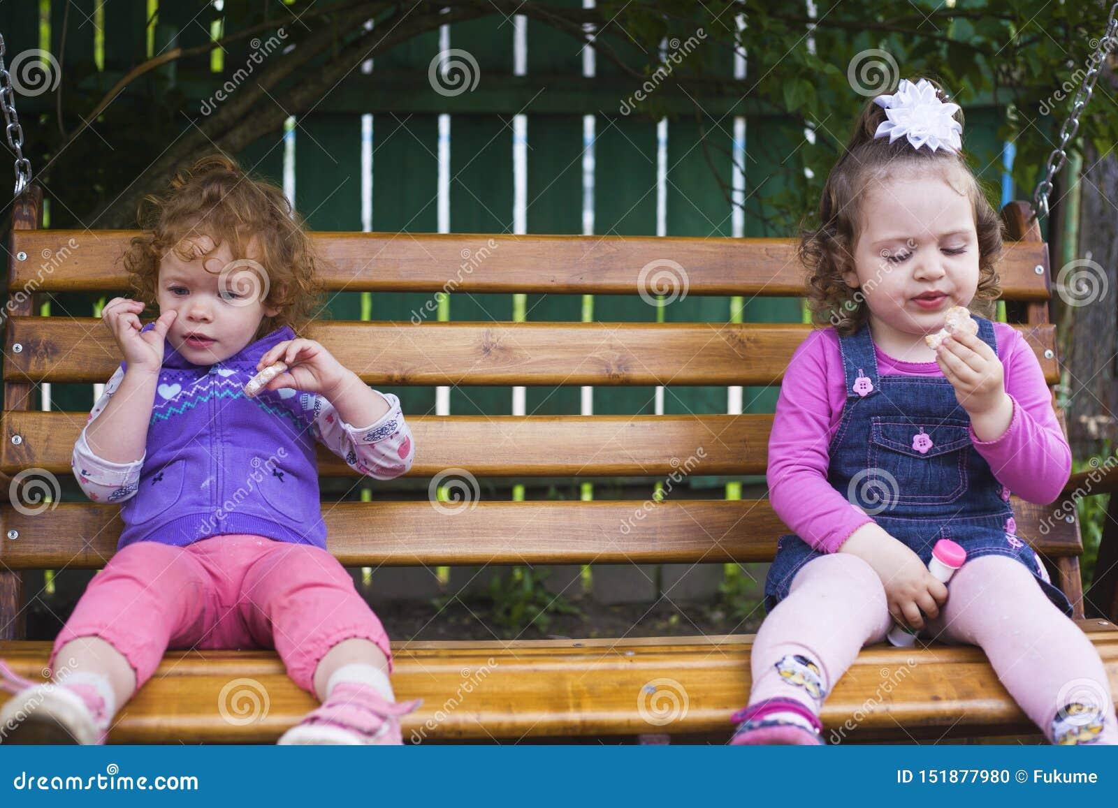 Deux petites filles s asseyent sur un banc accrochant et mangent des biscuits