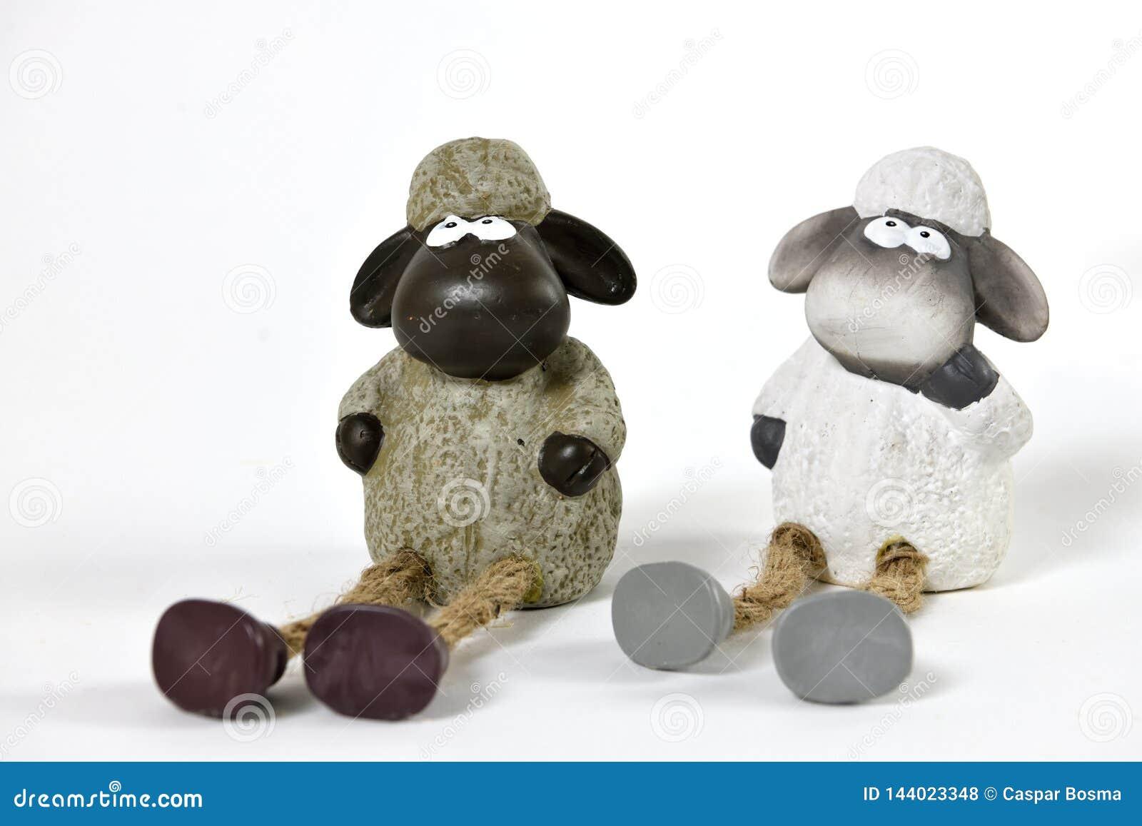 Deux petites poupées de moutons se reposant au sol