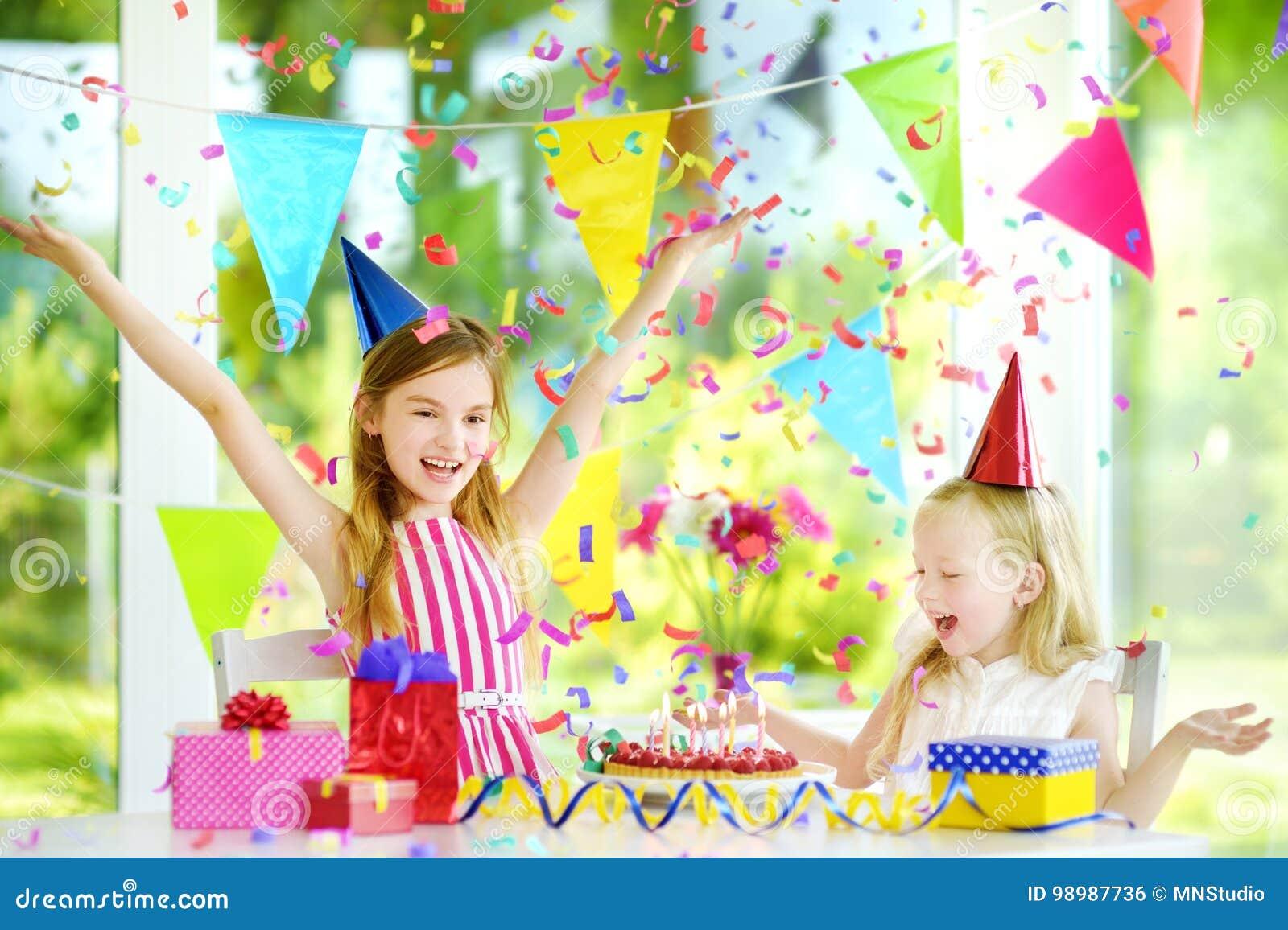 Deux petites soeurs drôles ayant la fête d anniversaire à la maison, soufflant des bougies sur le gâteau d anniversaire