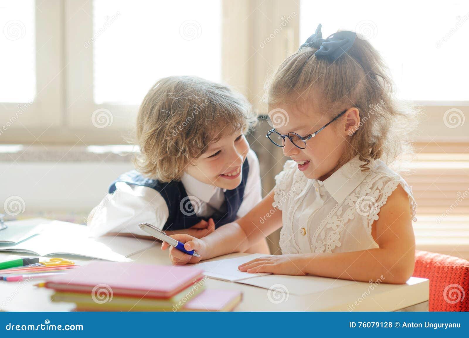 Deux petits camarade de classe, gars et girlie, se reposent au même bureau