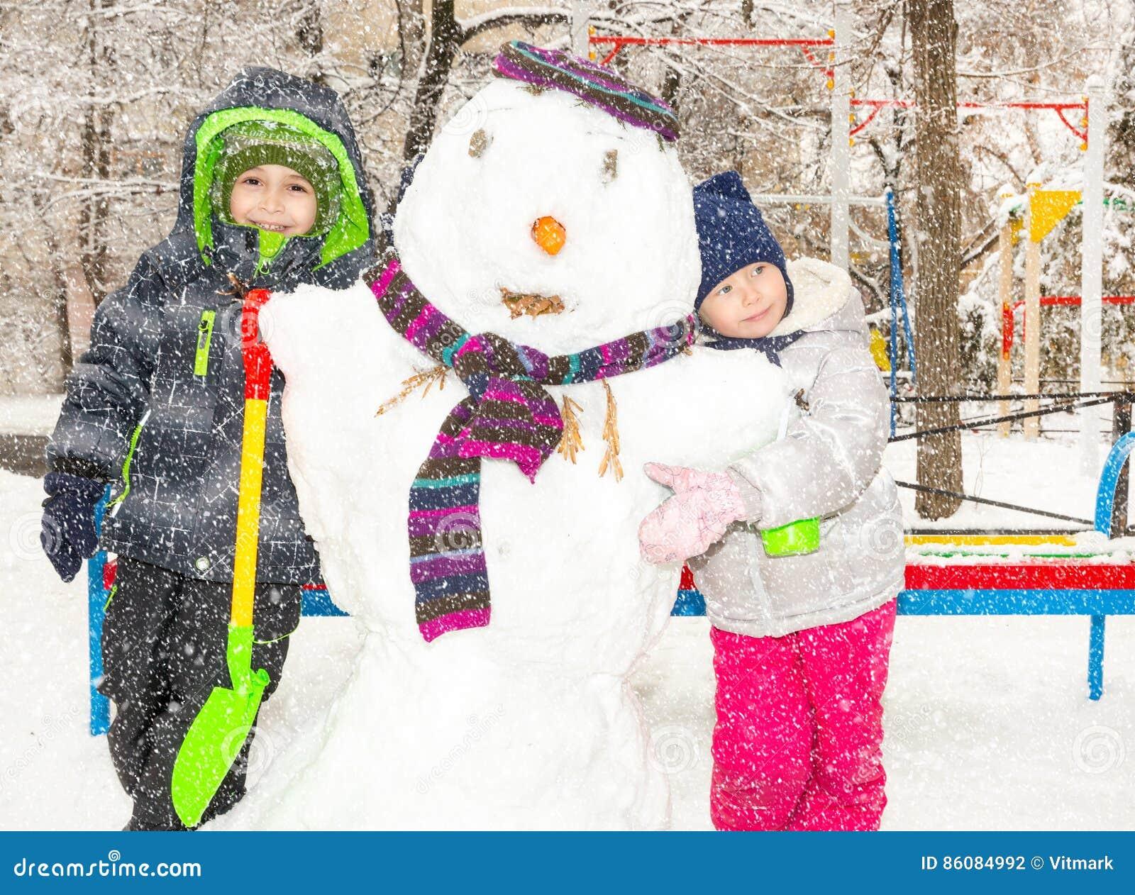 Deux petits démons, enfants faisant un bonhomme de neige, jouant et ayant l amusement avec la neige, extérieure le jour froid D A