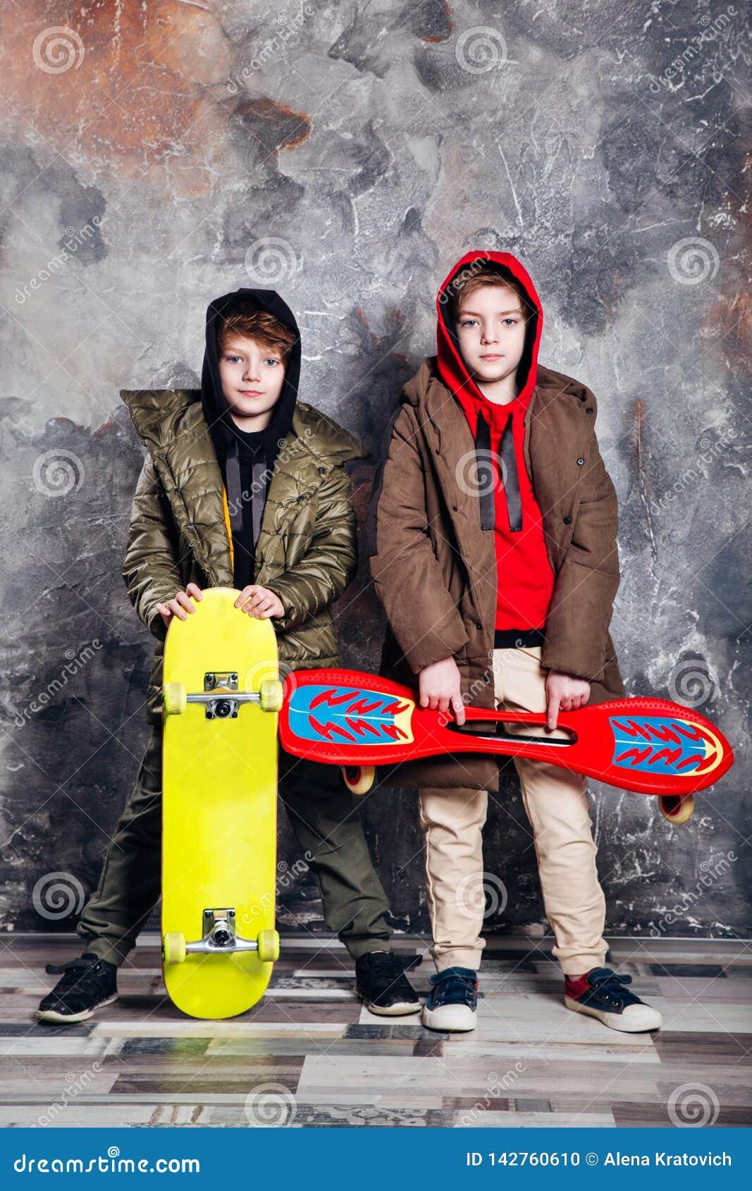 Deux petits garçons jumeaux dans des vêtements sport avec des planches à roulettes dans le studio Ado et concept de mode d enfant