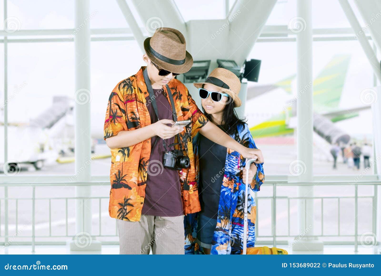 Deux petits touristes à l aide d un téléphone dans l aéroport