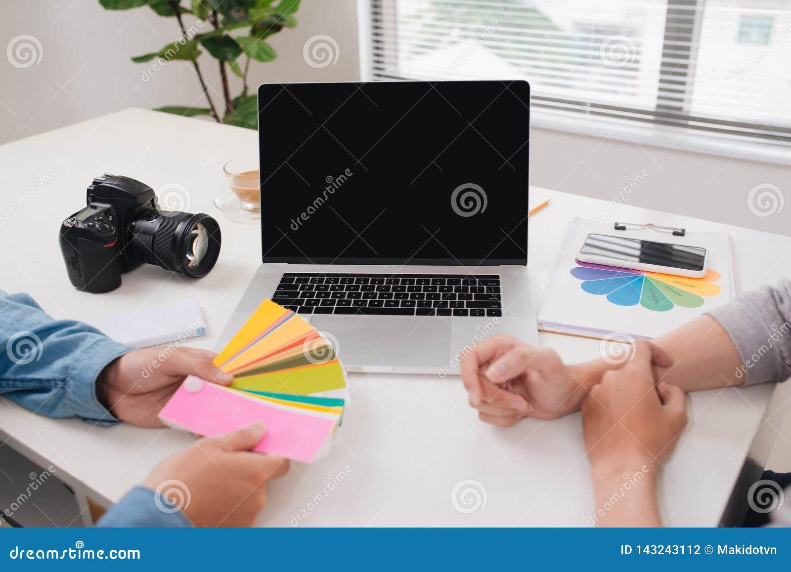 Deux photographes avec la caméra et l ordinateur portable fonctionnant dans le bureau