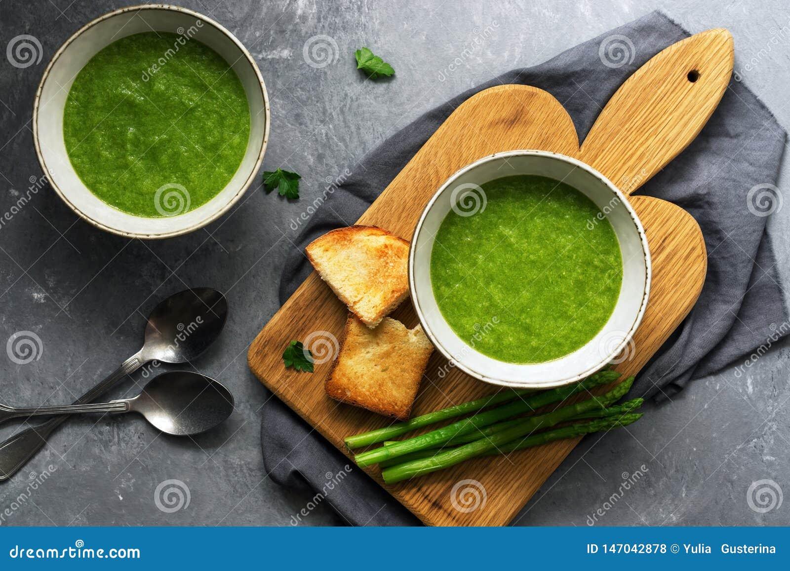 Deux plats de soupe à asperge, de végétarien et de nourriture crèmes verts faits maison de vegan Vue sup?rieure