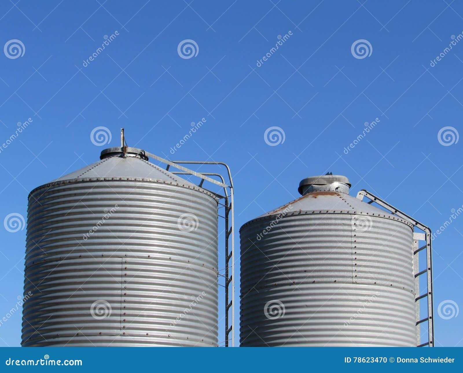 Deux poubelles de grain contre un ciel bleu