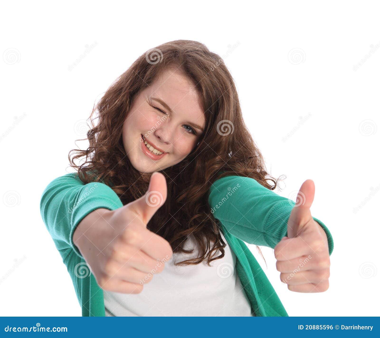 Deux pouces vers le haut pour la réussite par la fille de sourire d adolescent