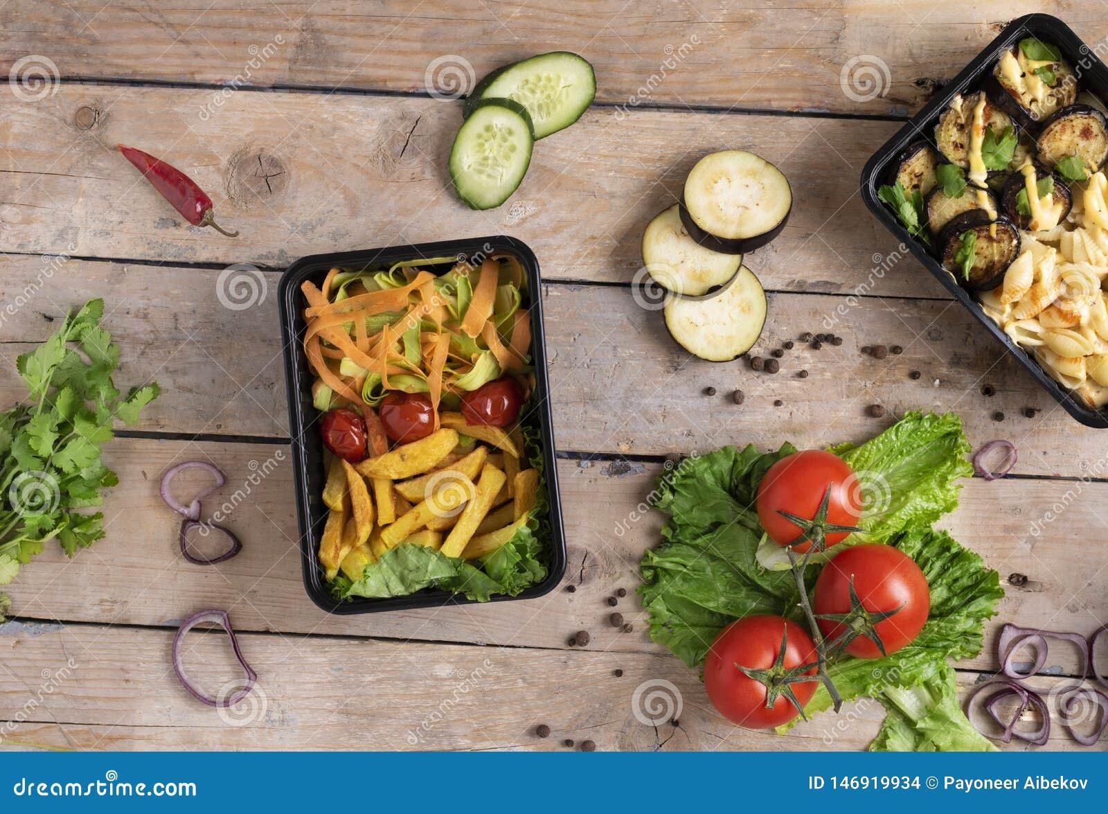 Deux récipients en plastique avec les ailes et les légumes crus de poulet grillés sur le fond, les légumes salade et les verts ru