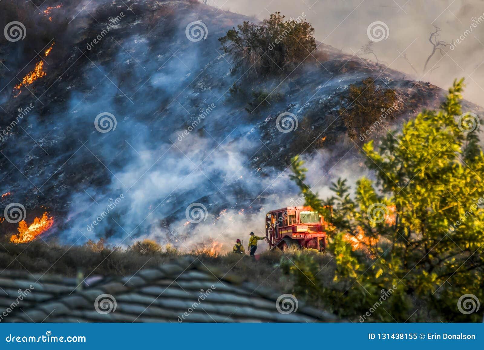 Deux sapeurs-pompiers se tiennent à côté du bouteur avec Hillside brûlant à l arrière-plan pendant le feu de la Californie