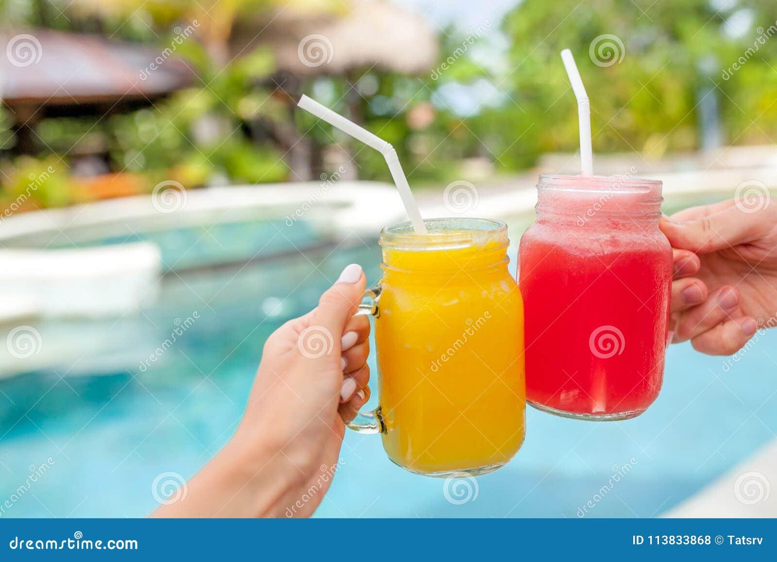 Deux secousses de fruit colorées dans des mains Été et humeur tropicale Smoothie de fruit mélangé par froid de boissons, de mangu