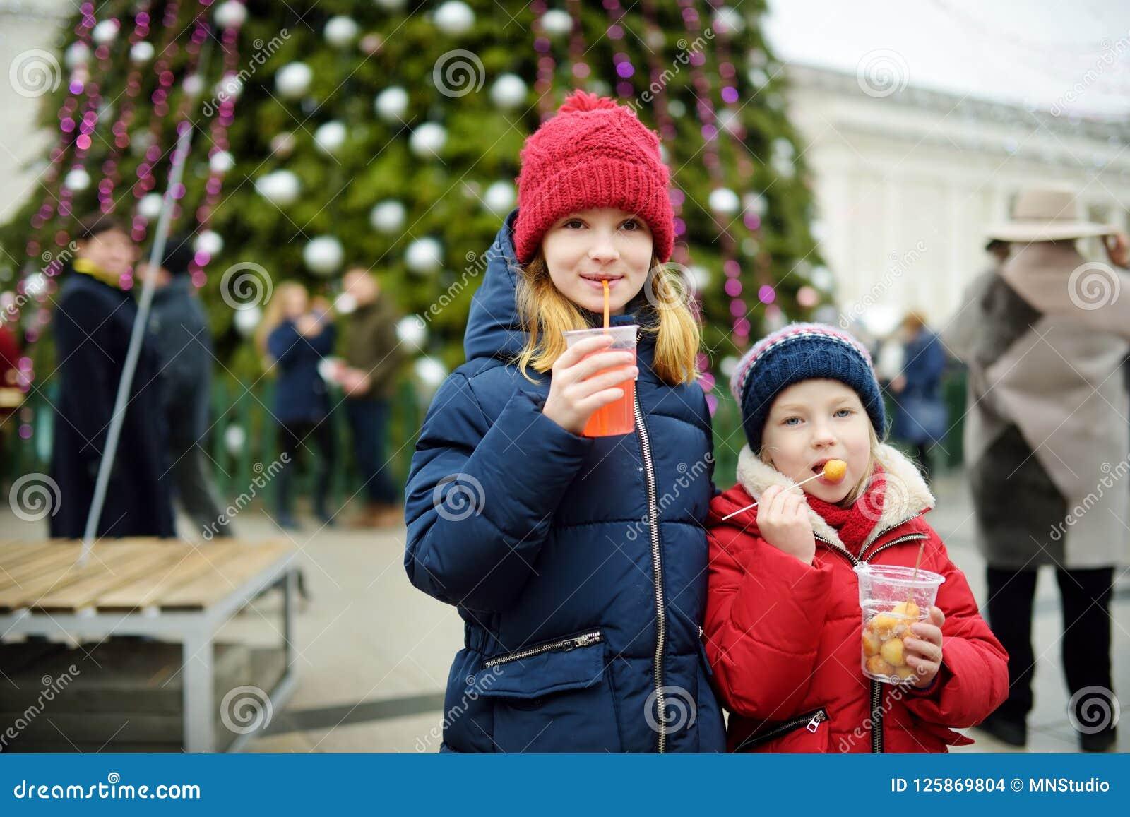 Deux soeurs adorables buvant du jus de pomme chaud sur le marché traditionnel de Noël