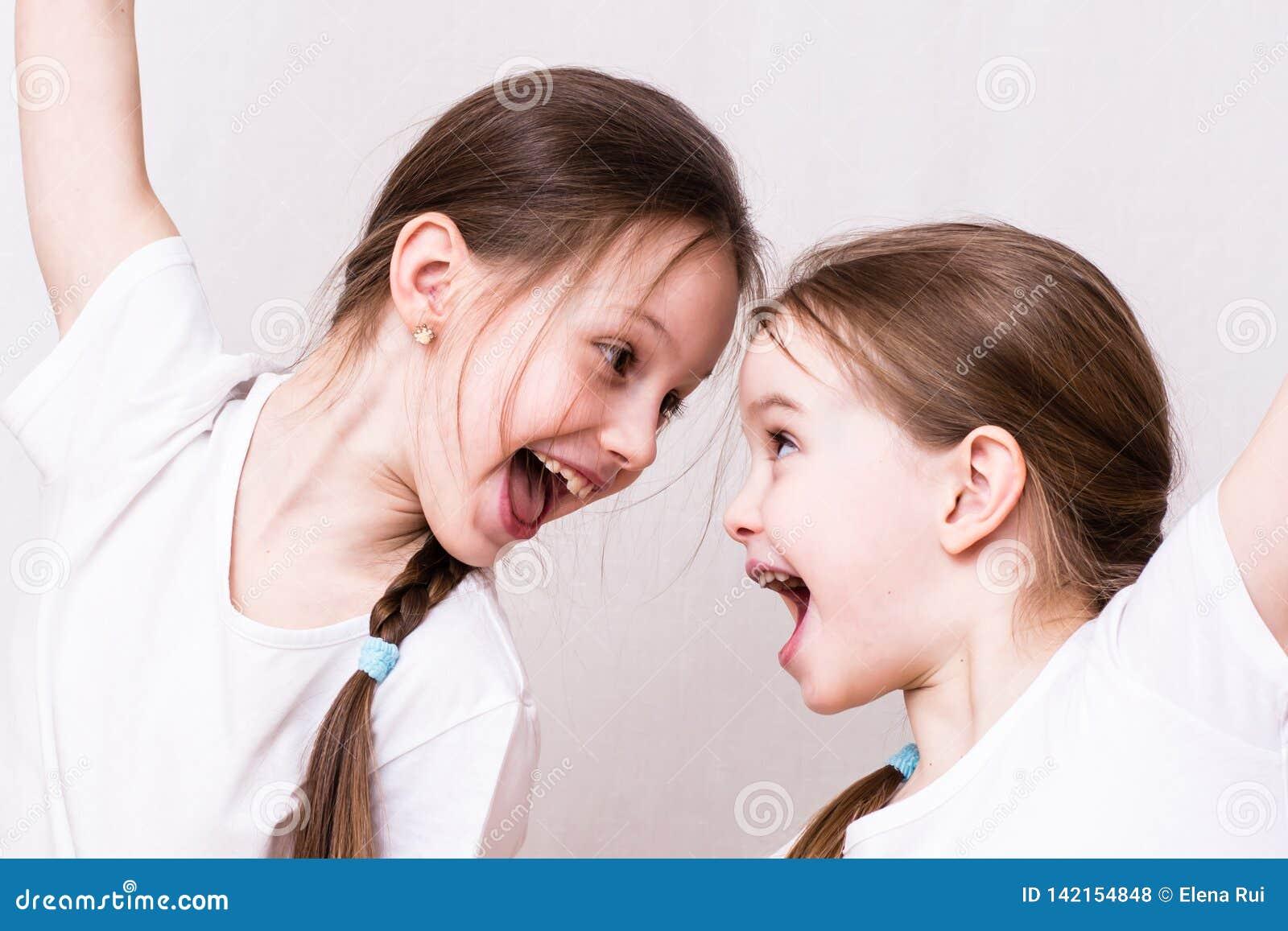 Deux soeurs de filles sourient avec émotion à l un l autre