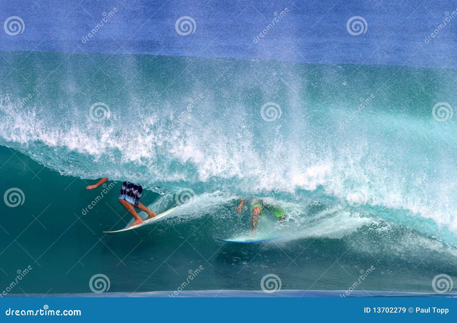 Deux surfers surfant dans une onde de tuyauterie
