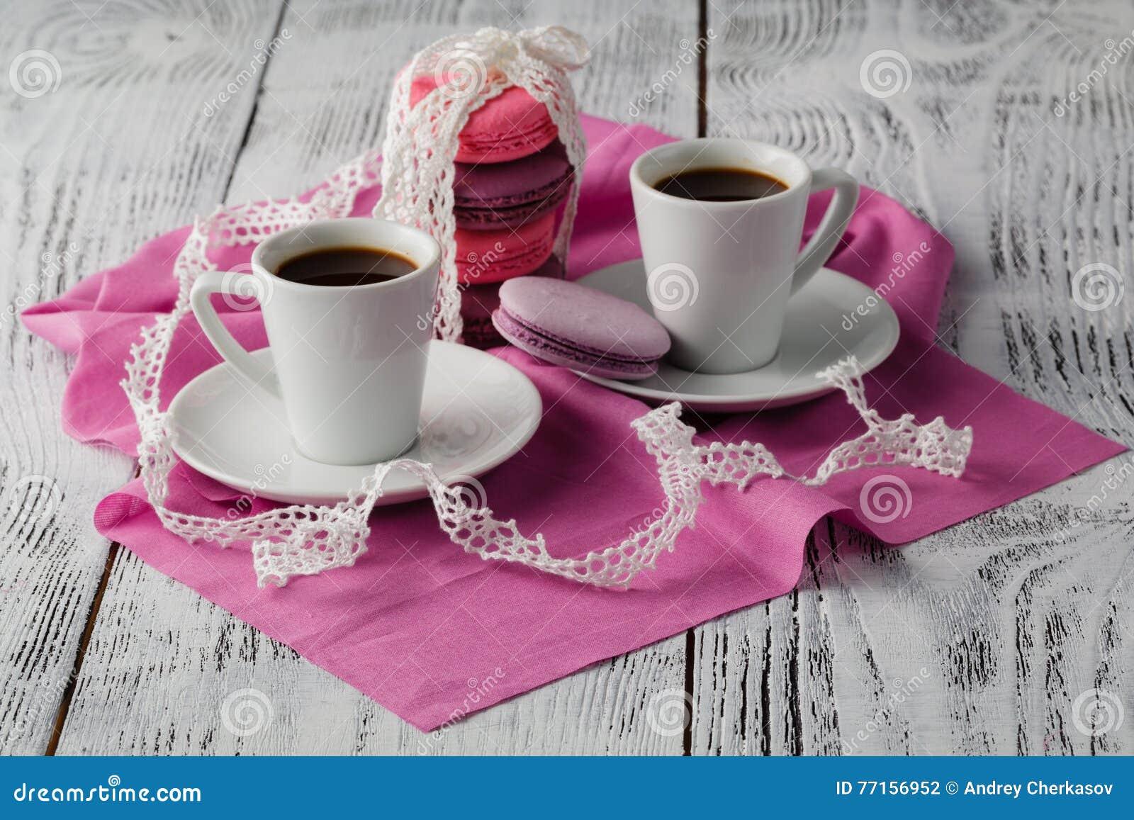 Deux tasses de café d expresso avec des macarons sur le fond rose