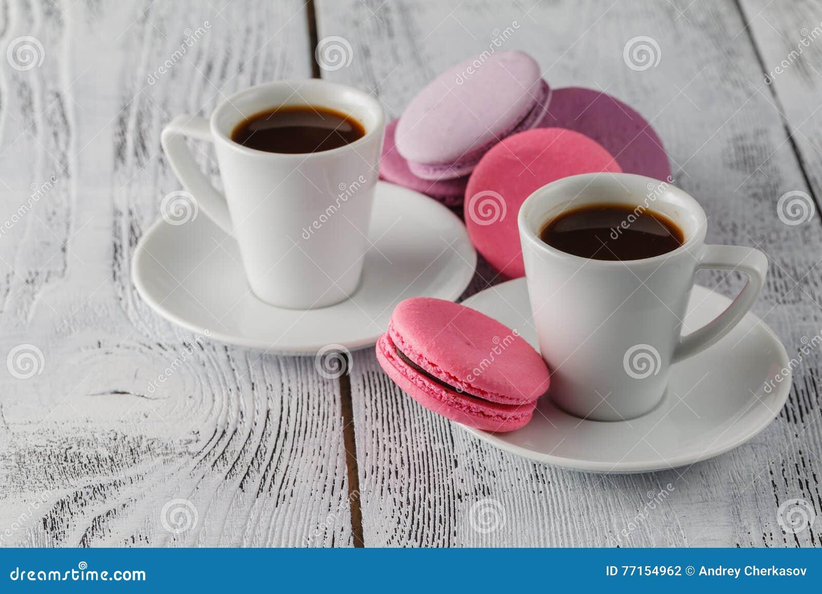 Deux tasses de café et de plan rapproché de macarons