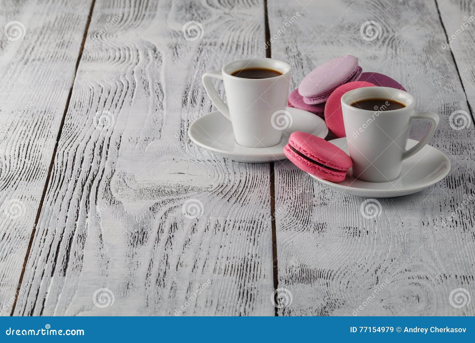 Deux tasses de café noir avec macarons délicieux