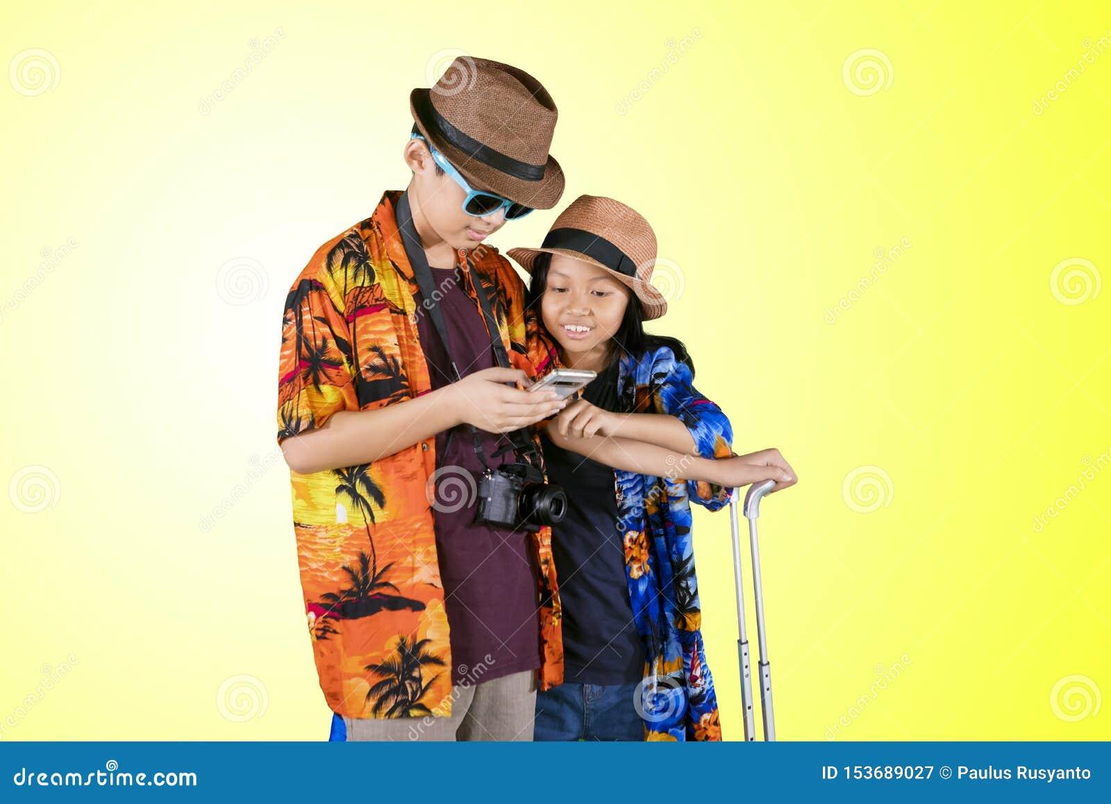 Deux touristes d enfant à l aide d un téléphone sur le studio