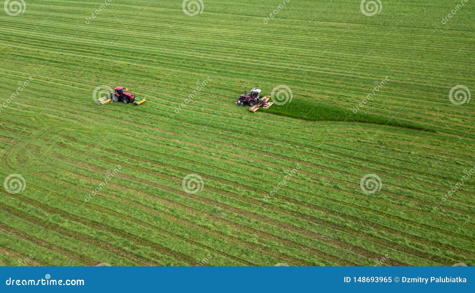 Deux tracteurs fauche l herbe sur une vue aérienne de champ vert