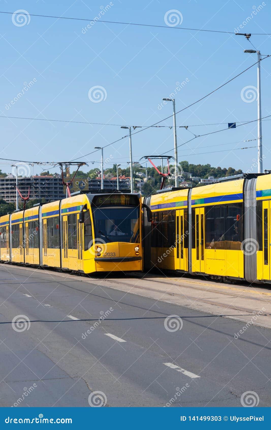 Deux tramways modernes jaunes à Budapest