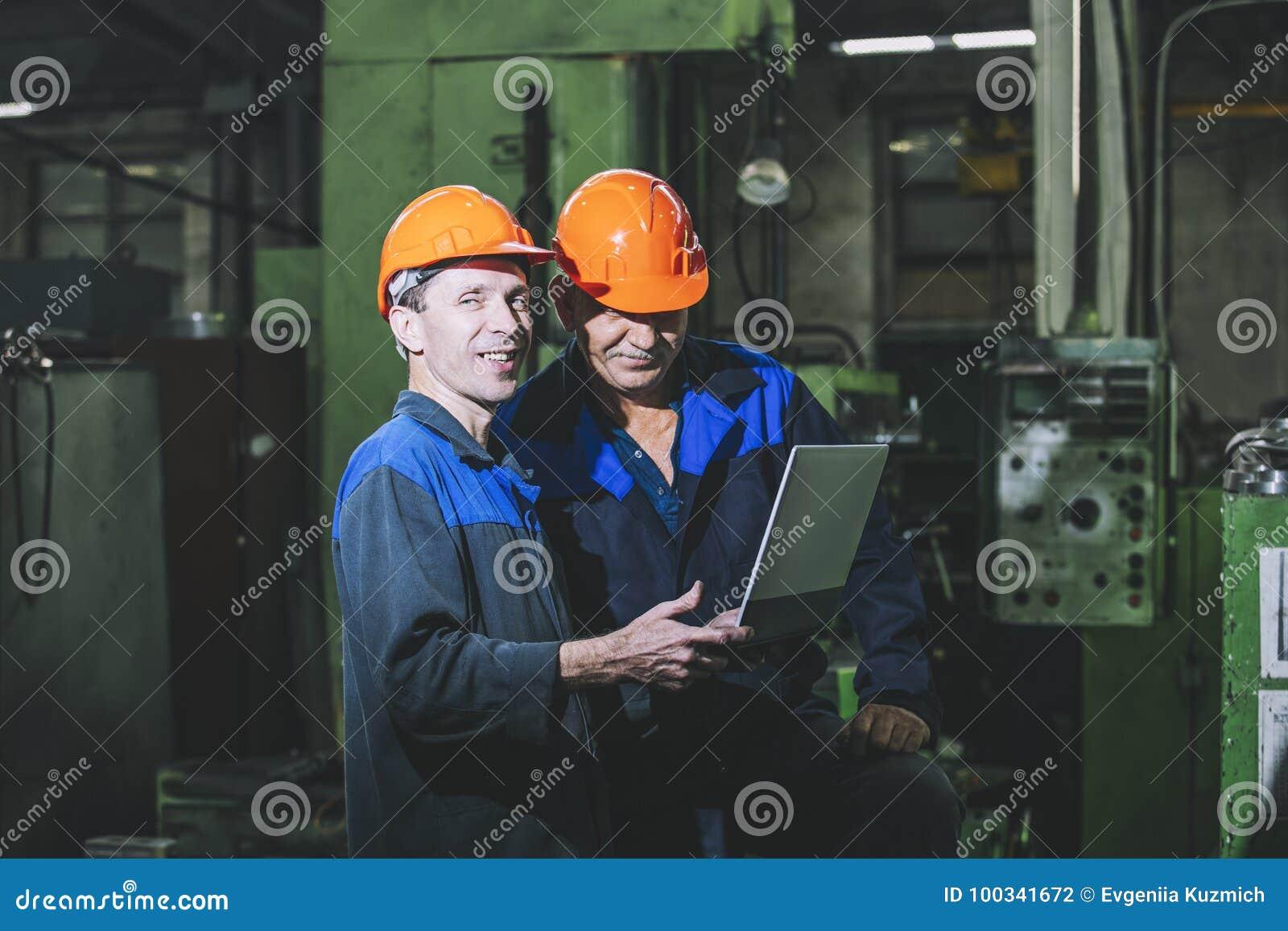Deux travailleurs à une usine avec un ordinateur portable à disposition sur le Th