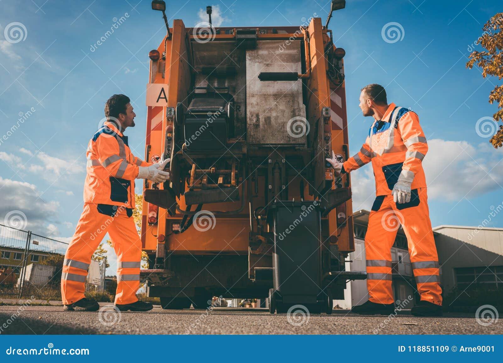 Deux travailleurs d enlèvement des ordures chargeant des déchets dans le camion de rebut