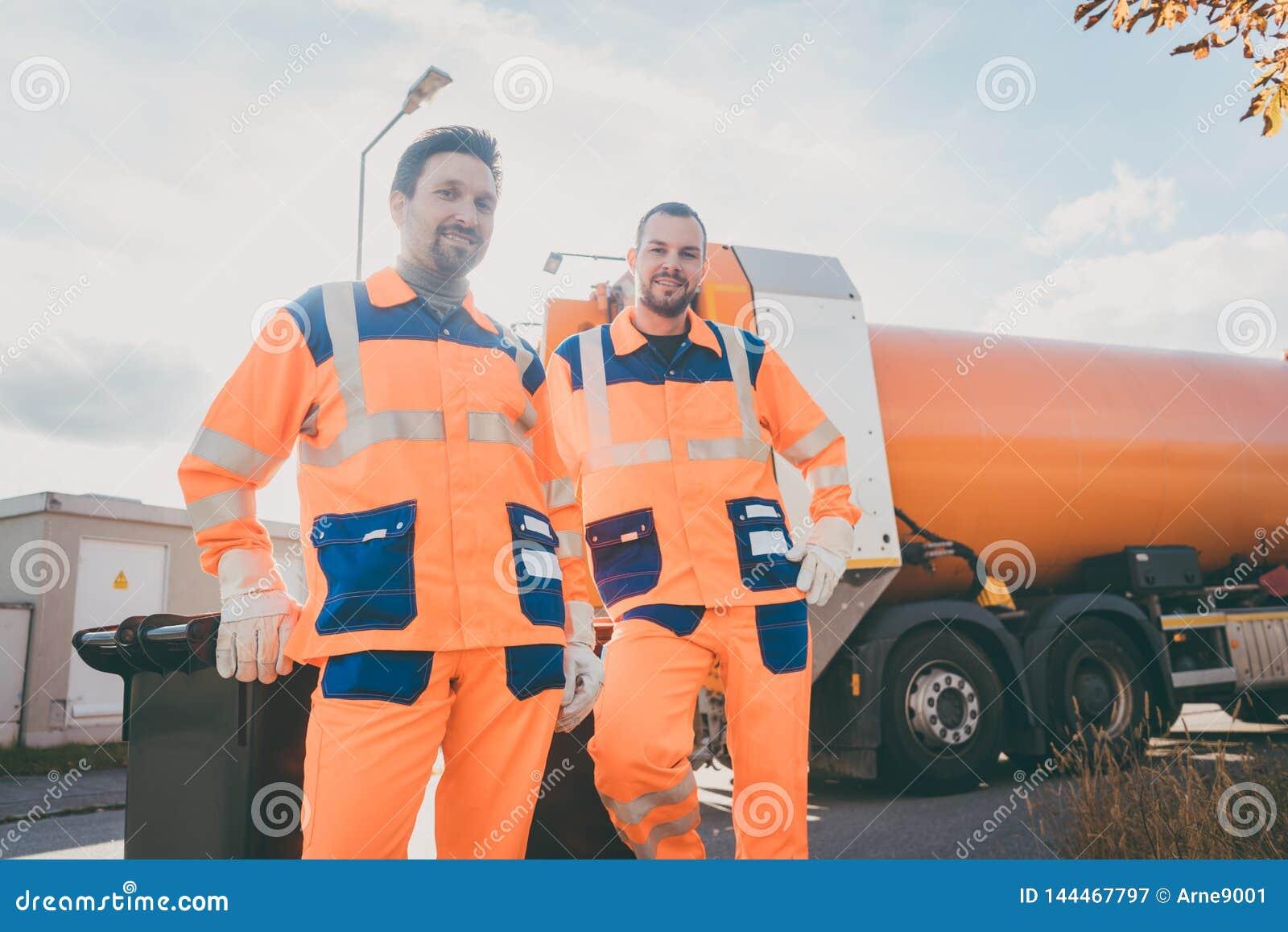 Deux travailleurs de service d enlèvement de déchets ayant la petite pause