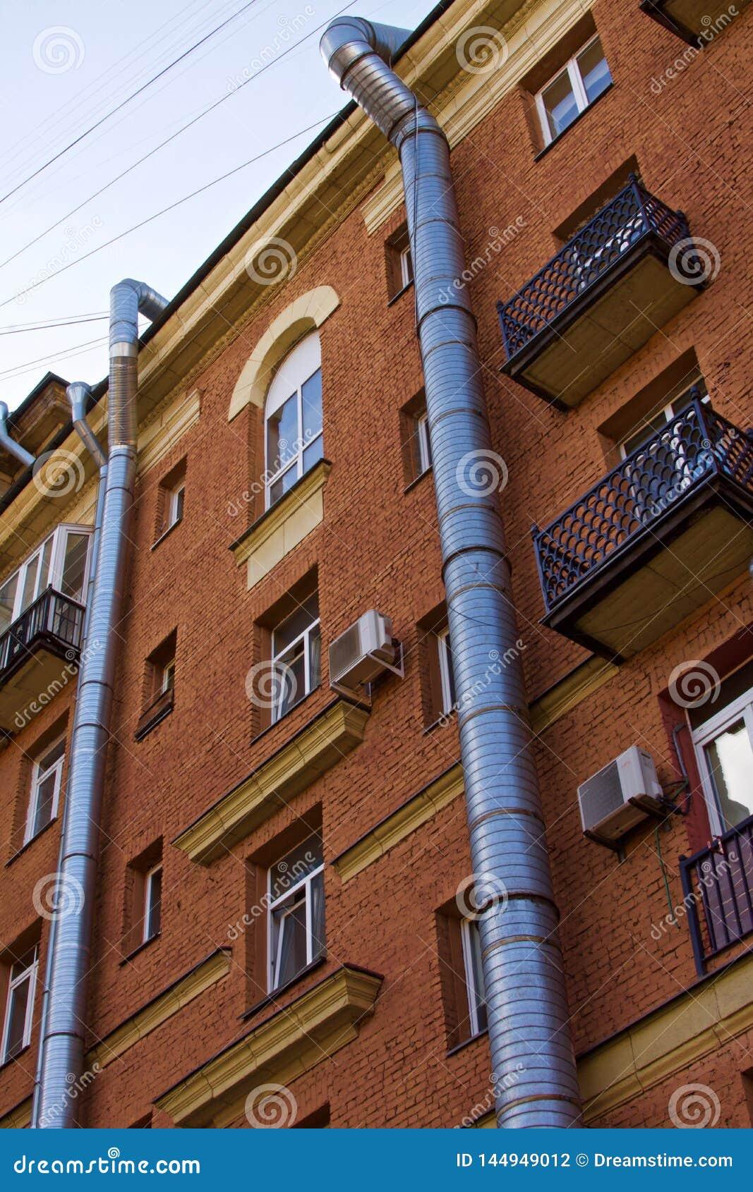 Deux tubes de aération métal-air courus le long de la façade d un immeuble de brique