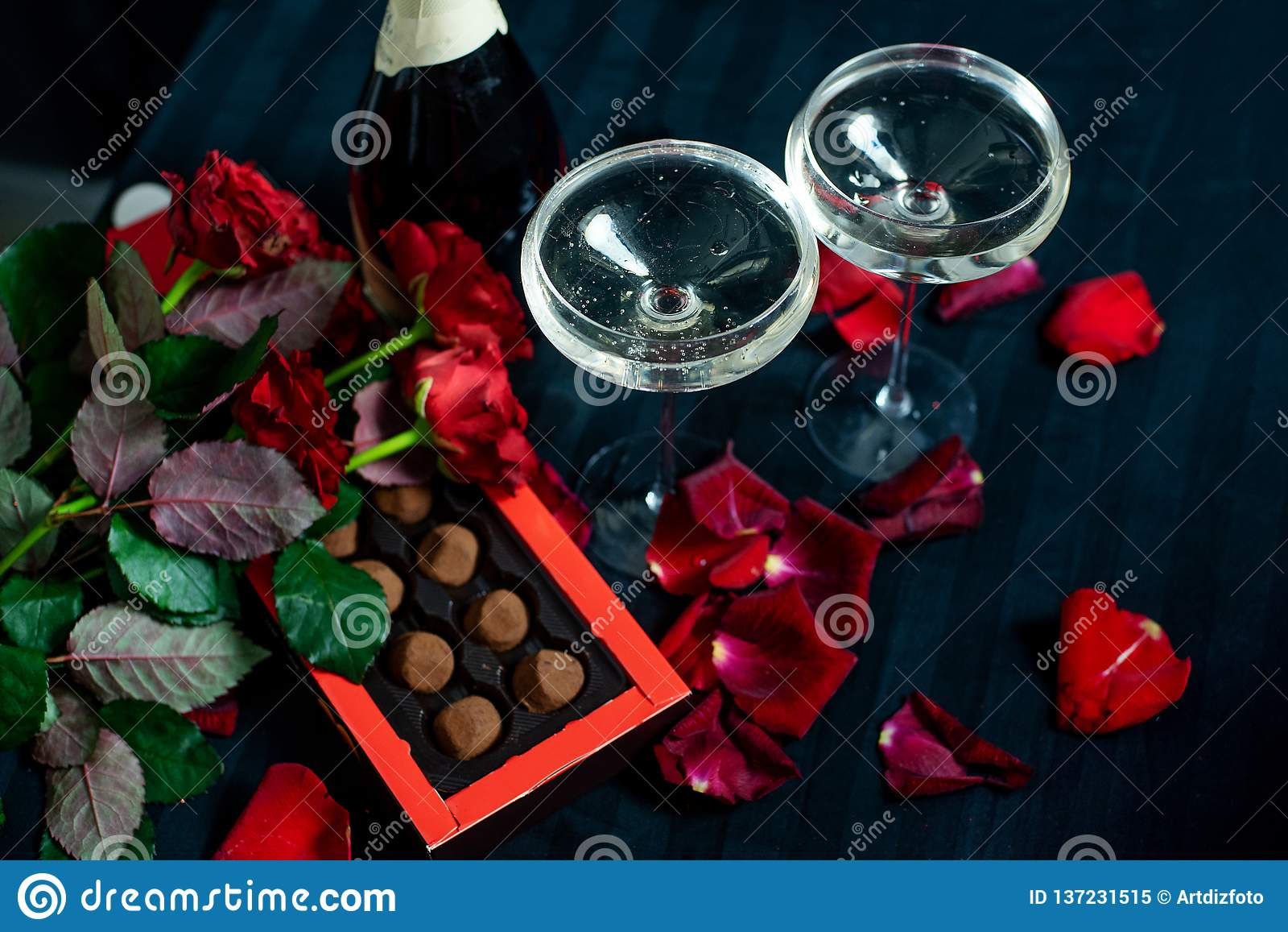 Deux verres de champagne, de roses rouges, de pétales et de chocolats sur un fond noir