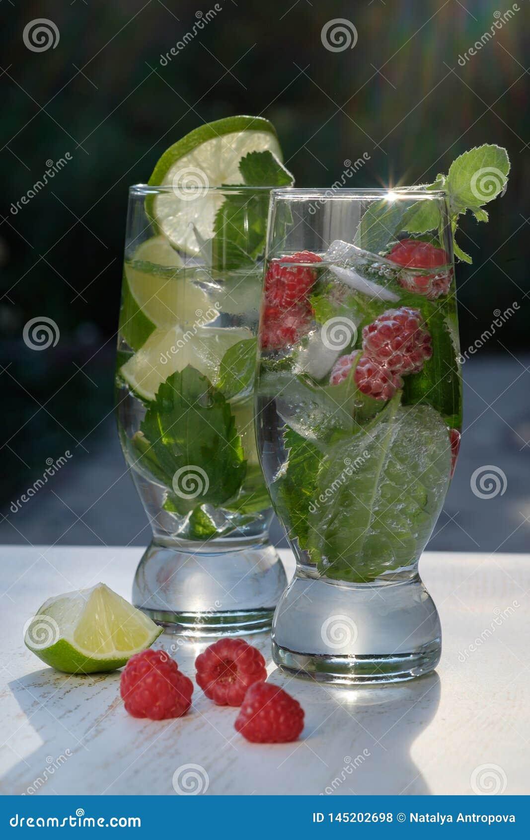 Deux verres de cocktail, de Mojito classique et de framboise Mojito au soleil