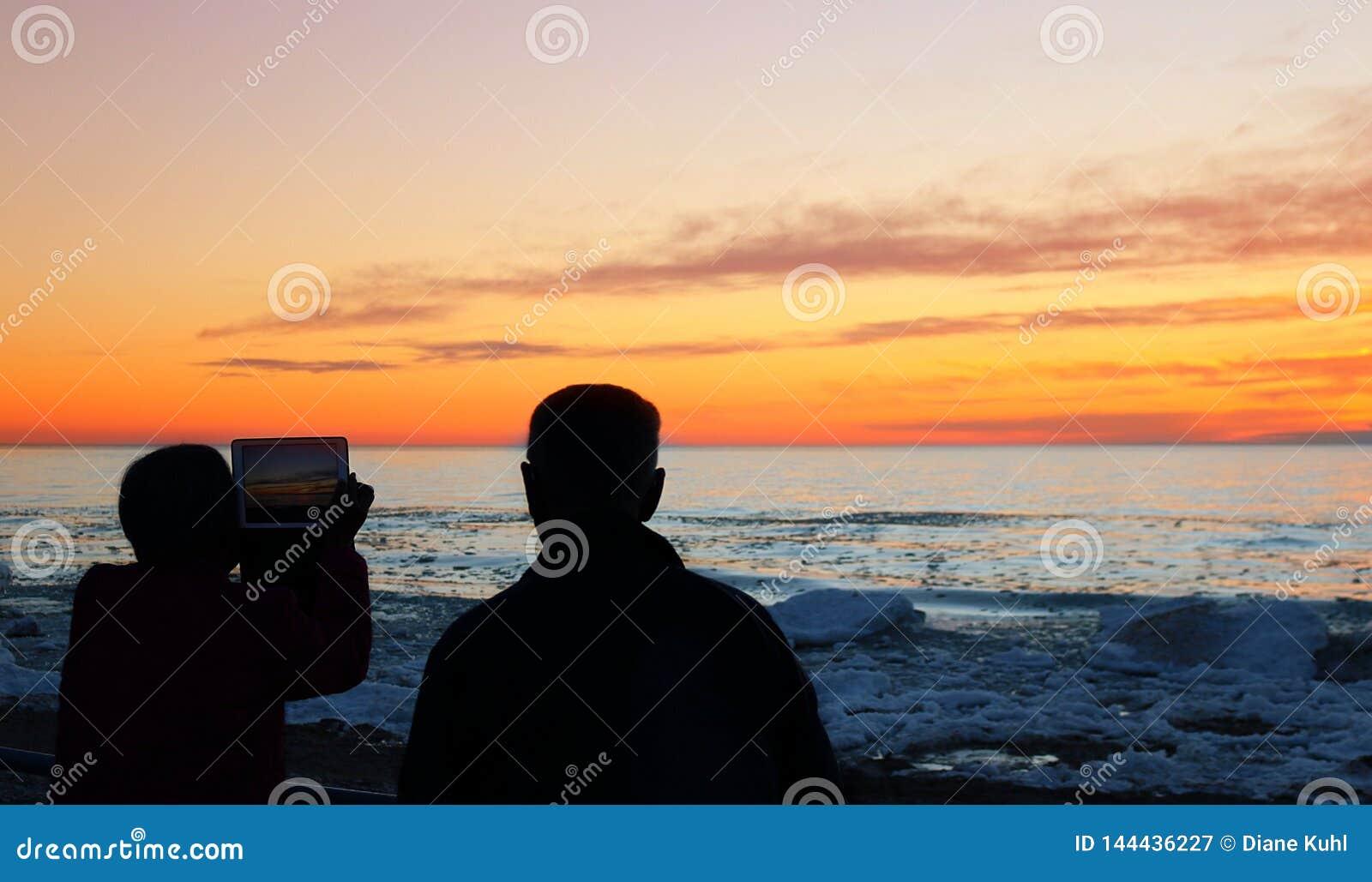 Deux vieillards utilisant la technologie pour capturer le coucher du soleil magnifique de ressort au-dessus du lac Huron