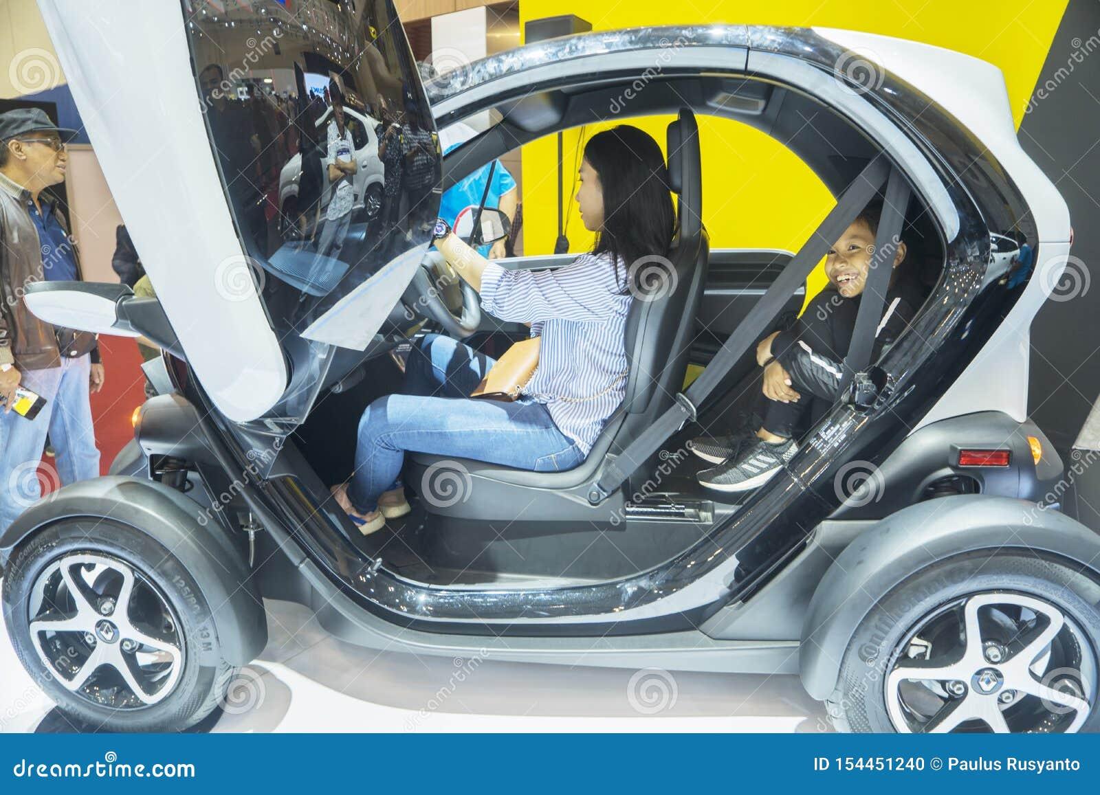 Deux visiteurs examinant la voiture de Renault Twizy