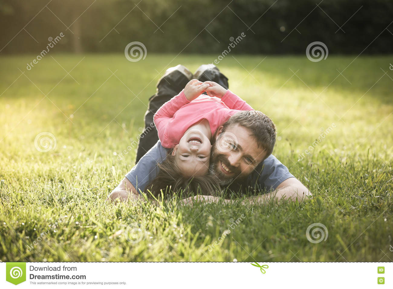 Devoted father and daughter lying on grass