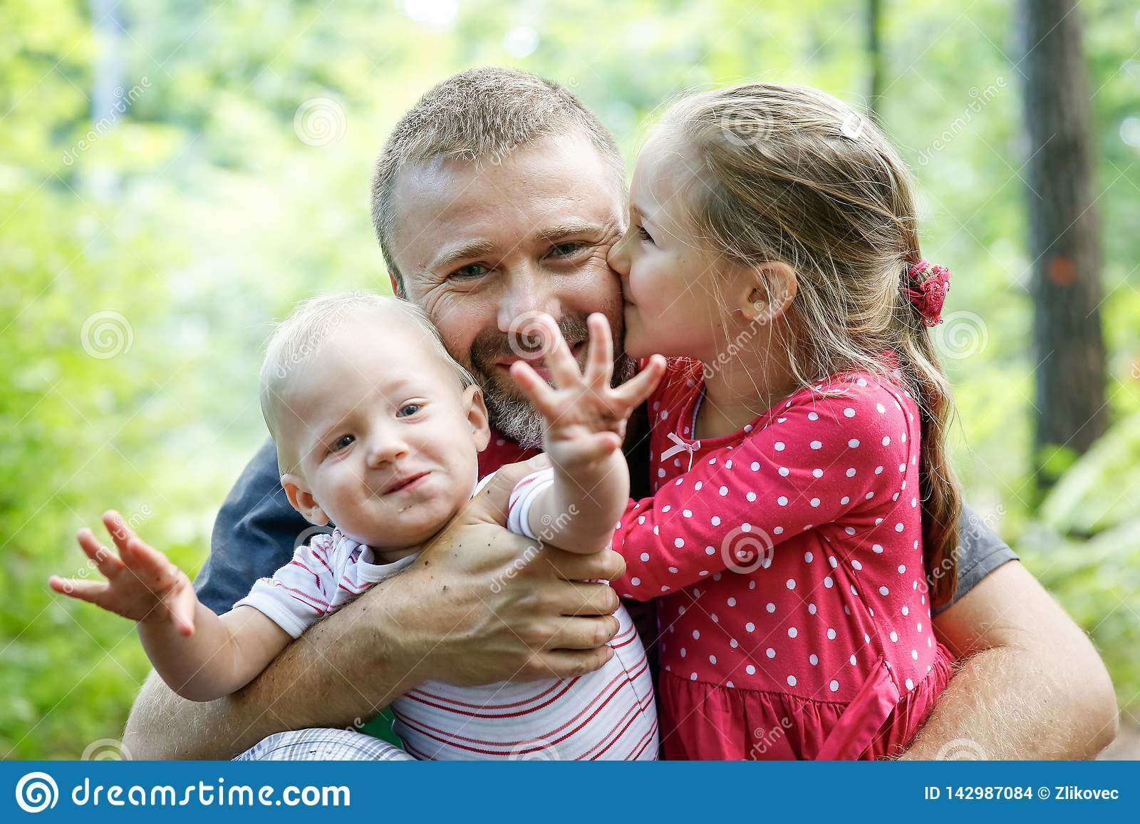 Devoted father hugging his son and daughter, enjoying the outdoor