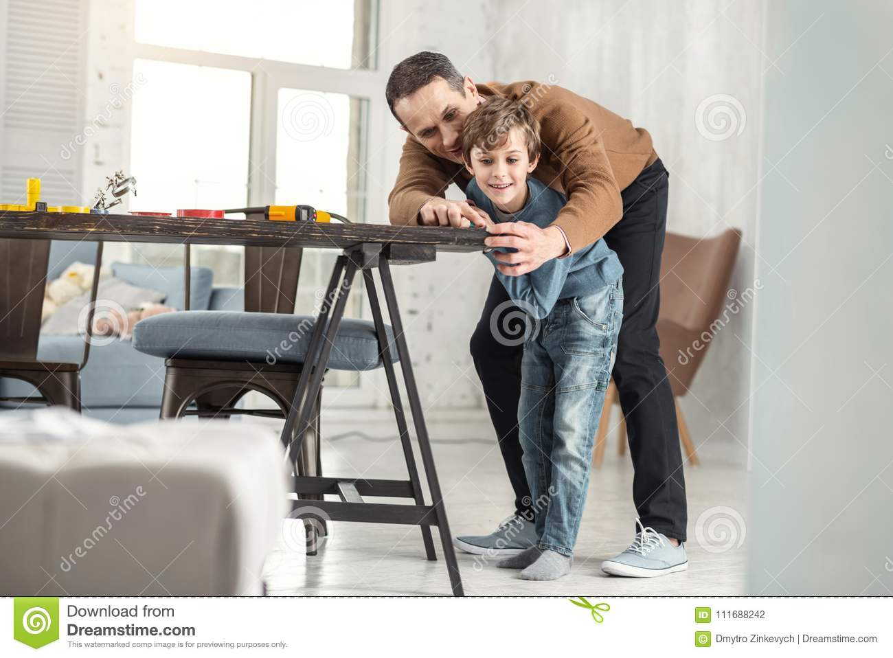 Happy Father Helping His Son Measure The Table Stock Photo