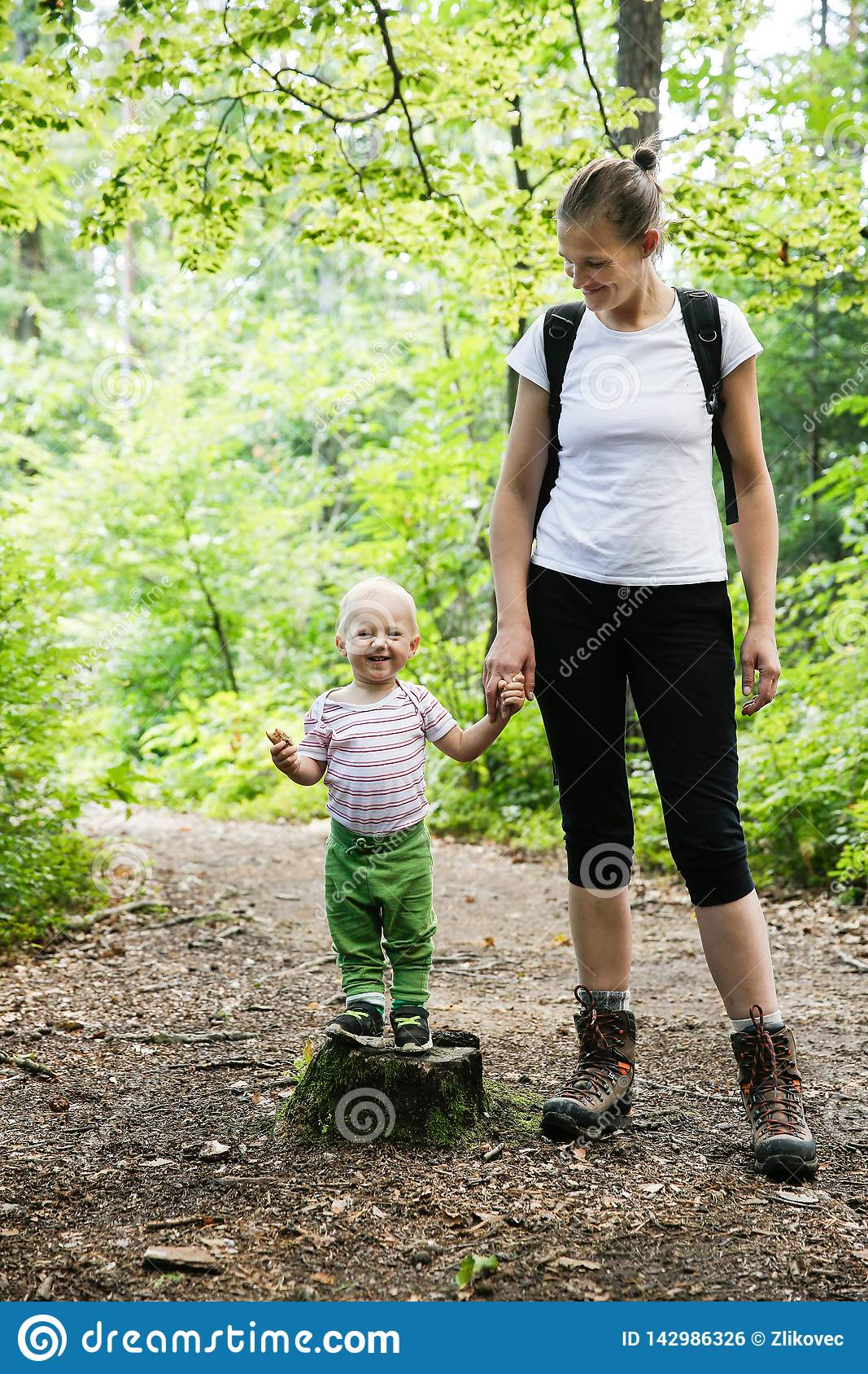 Devoted mother holding hands with her son, walking in the woods