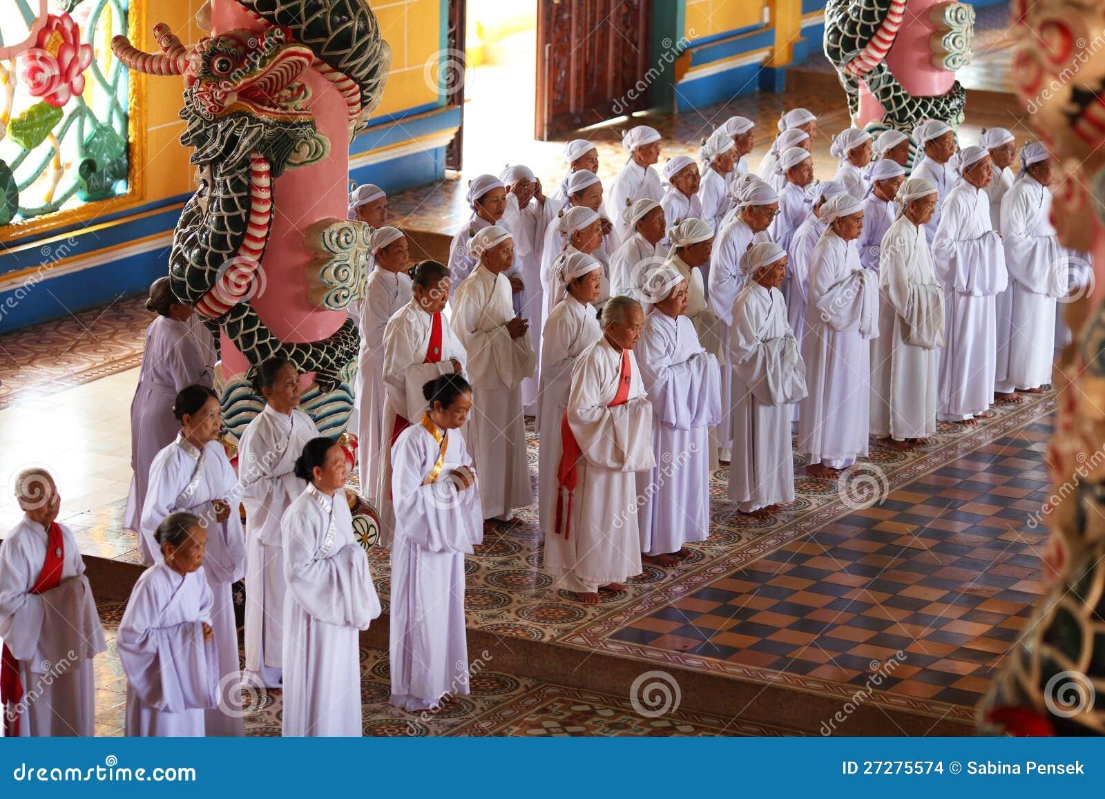 Devotos de las mujeres que ruegan en el templo de Cao Dai