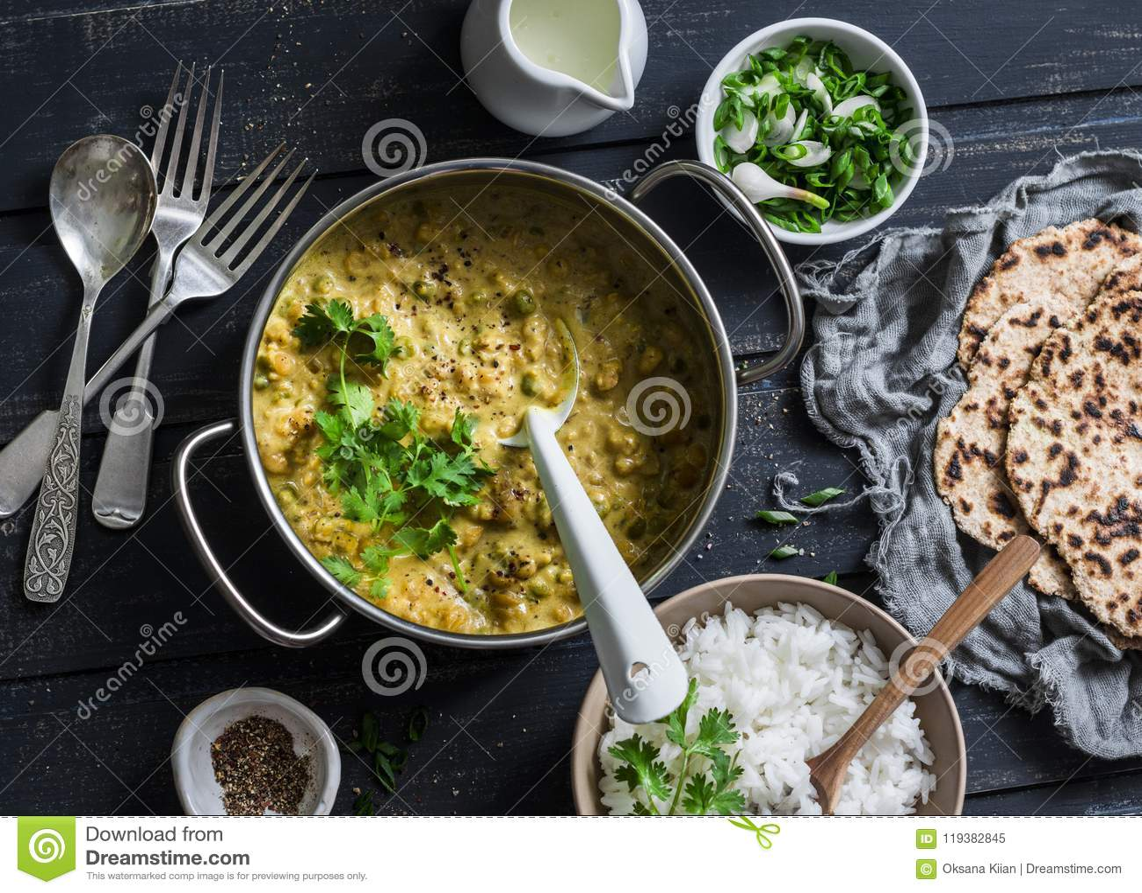 Dhal indiano nella cottura della pentola con il riso del gelsomino, il coriandolo e l intero flatbread del grano su fondo scuro,