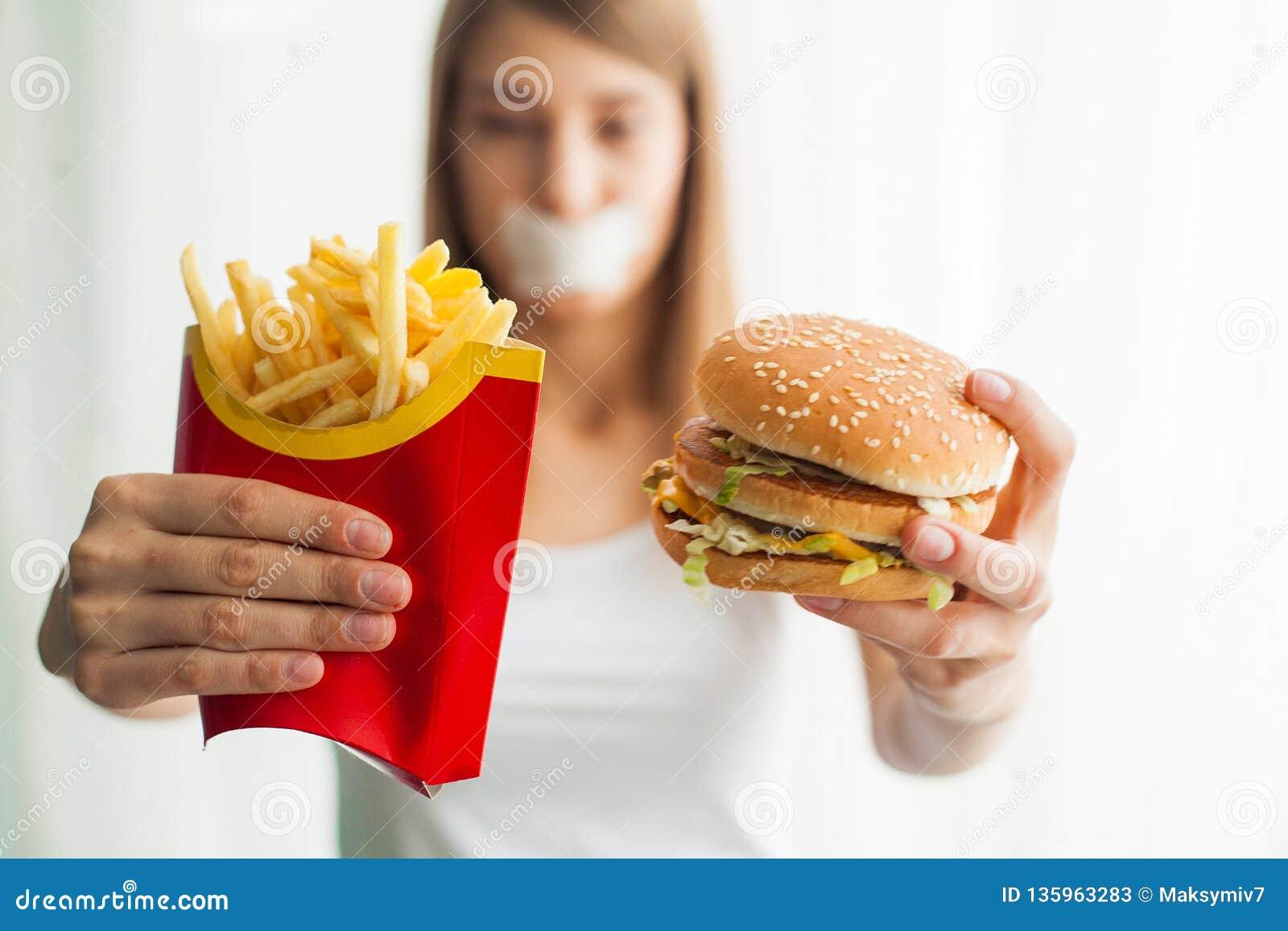 Diät Junge Frau mit Panzerklebeband über ihrem Mund, sie verhindernd, um ungesunde Fertigkost zu essen Gesundes Essenkonzept