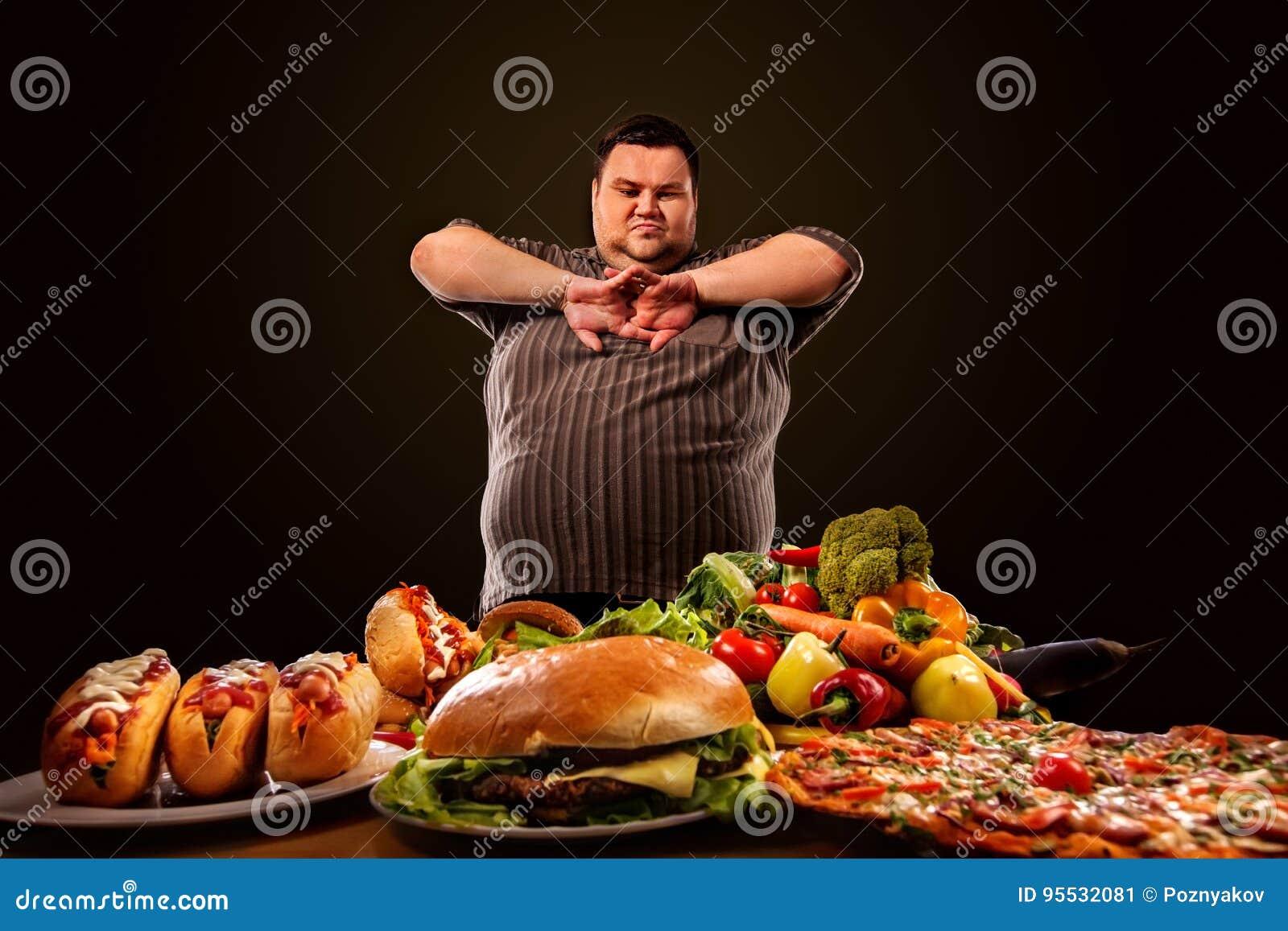 Diätdicker mann trifft Wahl zwischen gesundem und ungesundem Lebensmittel