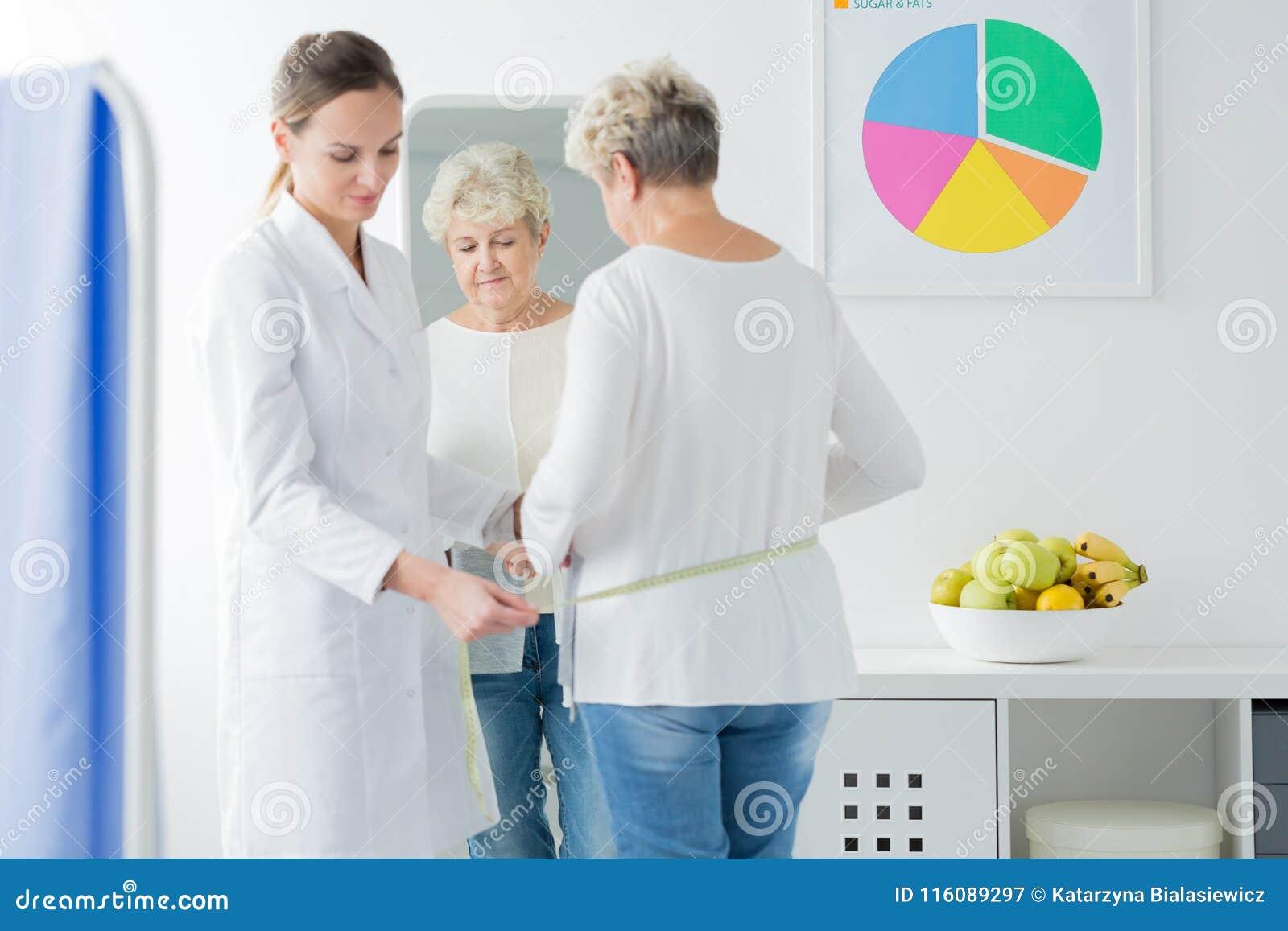 Diätetiker, der eine Frau misst