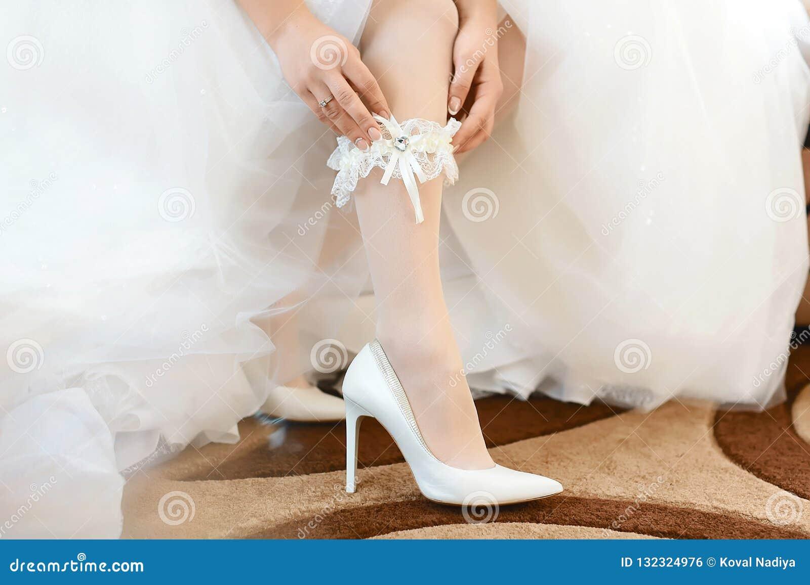 Di mattina, la sposa in calze e un vestito da sposa bianco in scarpe bianche del tallone indossa una giarrettiera sulla sua gamba