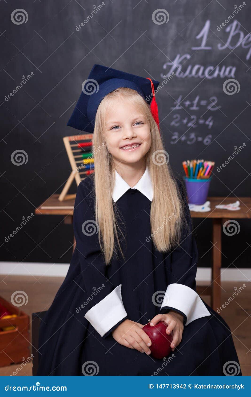 Di nuovo a scuola! Bambina allegra a scuola su un fondo nero Esaminando la macchina fotografica Concetto del banco Scolara nella
