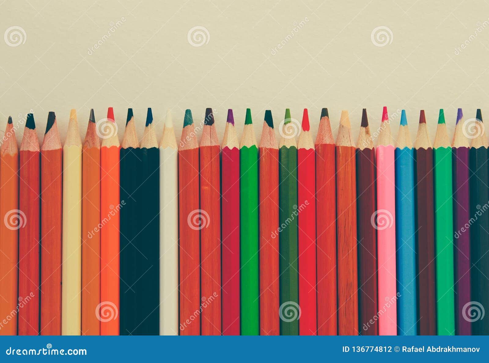 Di nuovo a scuola, concetto dalle matite colorate su un fondo giallo da carta strutturata per schizzare Tinto in un d avanguardia