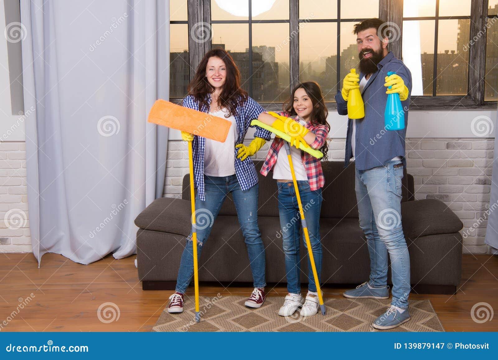Dia da limpeza Paizinho e filha da mamã da família com fontes de limpeza na sala de visitas Nós amamos a limpeza e a limpeza