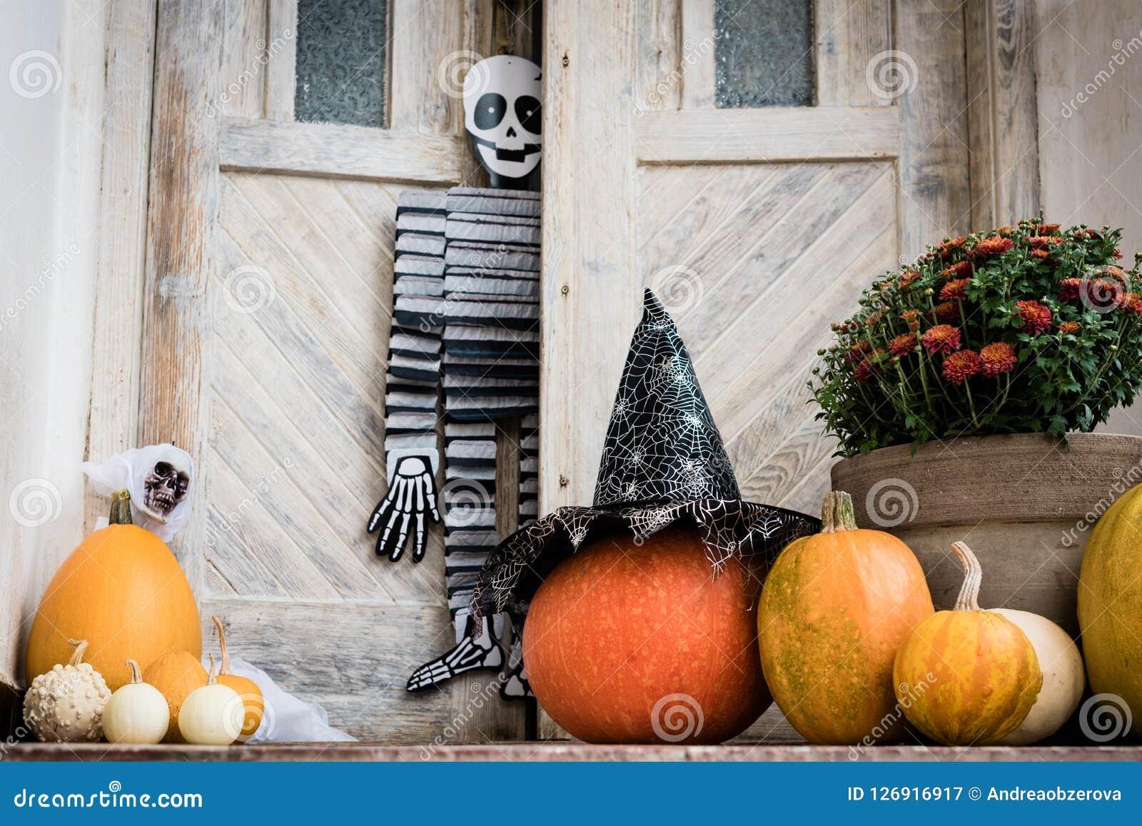Dia das Bruxas decorou a porta da rua com vário tamanho e abóboras e esqueletos da forma Front Porch decorou para Dia das Bruxas