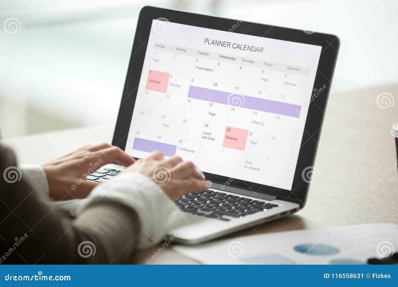 Dia do planeamento da mulher de negócios usando o calendário digital no portátil, clo