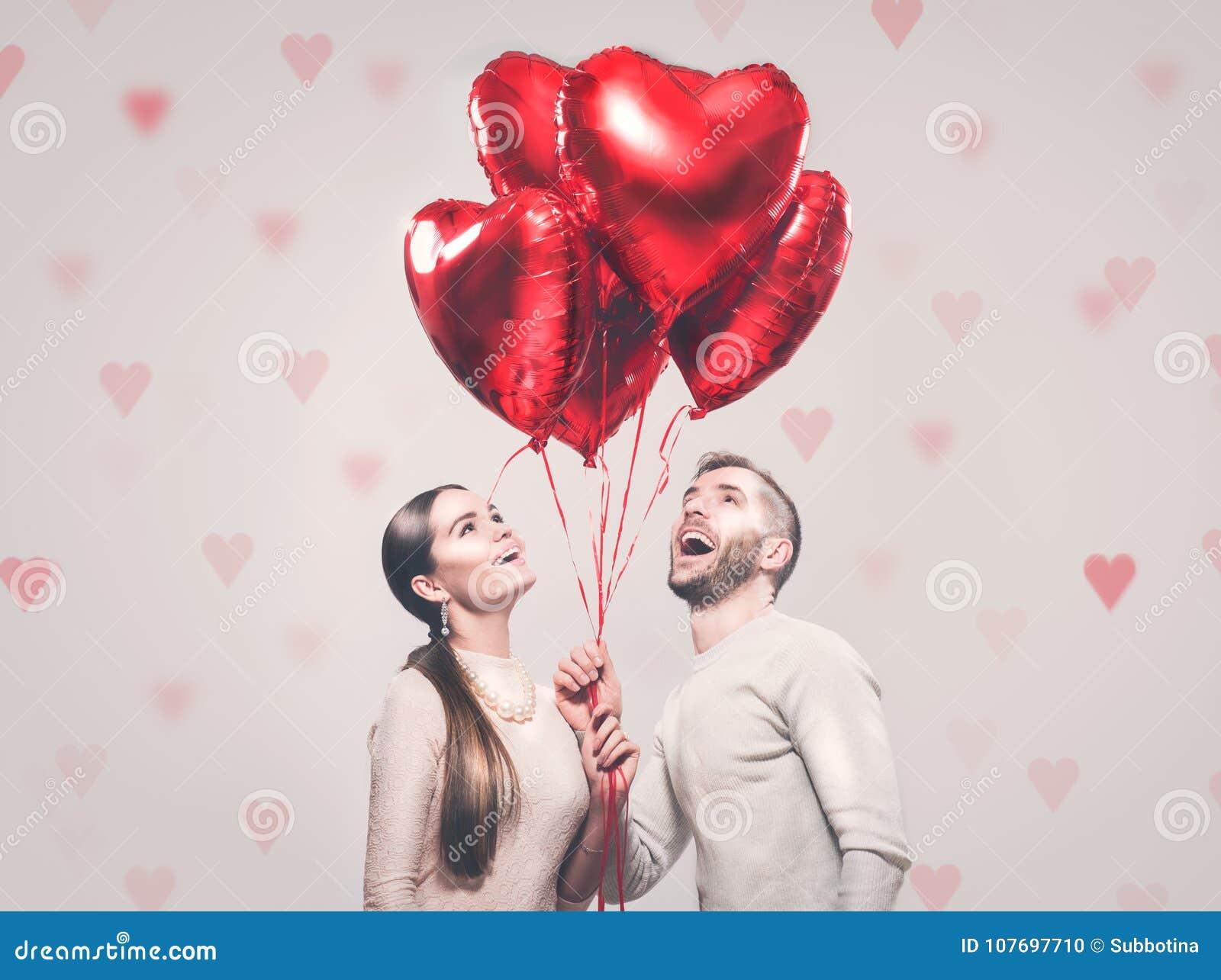 Dia do `s do Valentim Pares alegres felizes Retrato da menina de sorriso da beleza e de seu noivo considerável