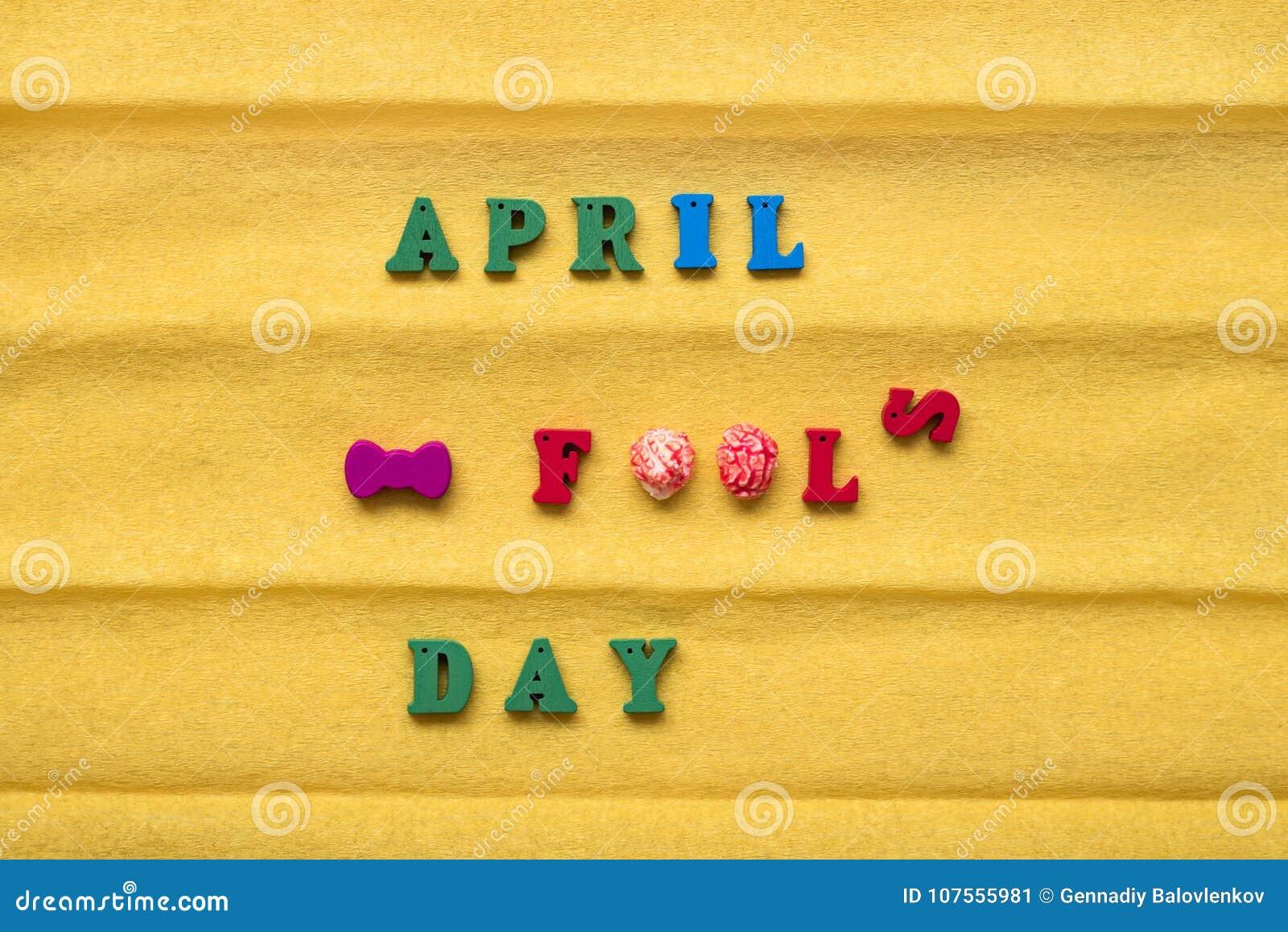 Dia do dia do tolo, inscrição das letras multi-coloridas em um fundo de papel amarelo