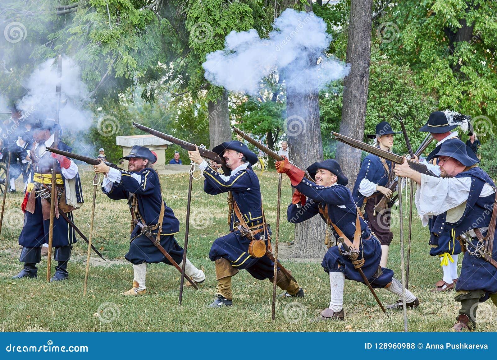 Dia histórico do reenactment de Brno Os atores na infantaria que histórica os trajes gravam um mosquete, fumo da pólvora são em t